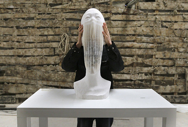 """Chinese artist Li Hongbo shows his paper sculpture work, which is made of 6,000 pieces of paper, while raising it at his studio on the outskirts of Beijing, January 20, 2014. Born into a simple farming family, Li said he had always loved paper, invented in ancient China. Beyond his sculptures, he has spent six years producing a collection of books recording more than 1,000 years of Buddhist art on paper. Neither plaster nor clay, the statues are concertinas of thousands upon thousands of fine pieces of paper.""""At the beginning, I discovered the flexible nature of paper through Chinese paper toys and paper lanterns,"""" Li, 38, told Reuters. Picture taken on January 20, 2014. REUTERS/Jason Lee (CHINA - Tags: SOCIETY) - RTX17QY9"""
